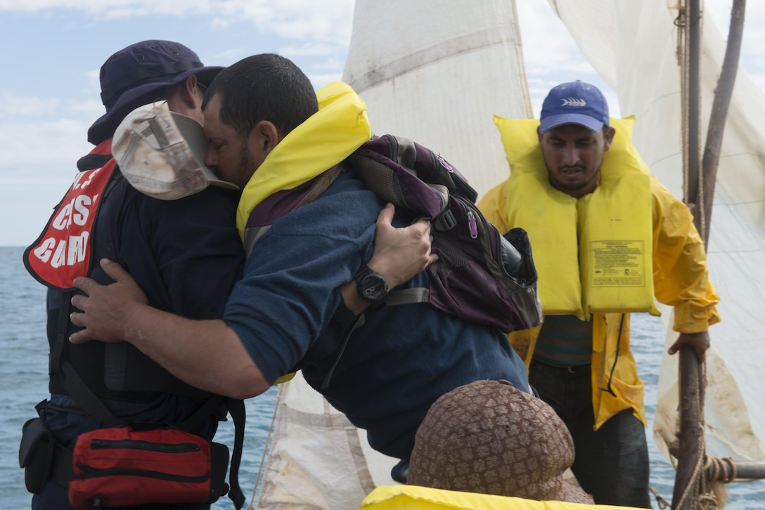 Coast Guard Petty Officer 1st Class Jorge Canedo, a certified Spanish interpreter and crewmember aboard the Coast Guard Cutter Kathleen Moore, assists a Cuban man to a Coast Guard small boat in the Caribbean Sea, Dec. 9, 2015. In the course of three days the crew of the Kathleen Moore interdicted 50 Cuban migrants allegedly attempting to enter the U.S. illegally. (U.S. Coast Guard photo by Petty Officer 3rd Class Ashley J. Johnson)