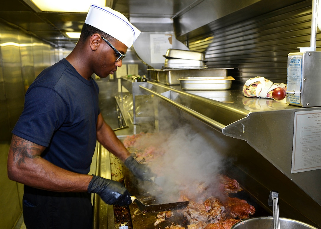 Navy Culinary Specialist 3rd Class Traivon Smart grills meat in the galley aboard the amphibious dock landing ship USS Whidbey Island (LSD 41) Aug. 9. DLA Troop Support's Subsistence supply chain hosted a pre-proposal conference Sept. 28 to help vendors preparing proposals for an upcoming beef national contract