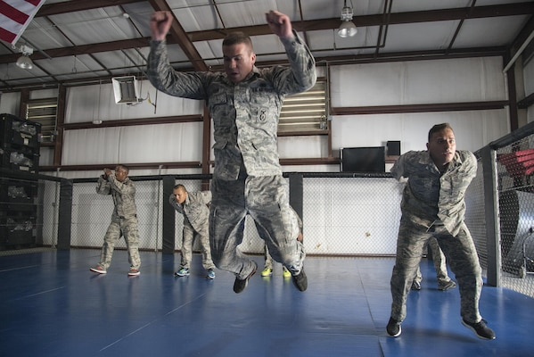 Staff Sgt. Neal Kiser and Senior Airman Andrew Deno, 902nd Security Forces Squadron, jump as a part of physical exercise during compatives training Sept. 14 at Joint Base San Antonio-Randolph. Kimura and Americana submission holds are often seen in mixed martial arts matches, but now they're also commonplace in Hangar 52 at Joint Base San Antonio-Randolph.