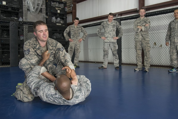 Staff Sgt. Matthew Cummings, 902nd Security Forces Squadron combatives instructor, demonstrates a mount position during training Sept. 14 at Joint Base San Antonio-Randolph. Kimura and Americana submission holds are often seen in mixed martial arts matches, but now they're also commonplace in Hangar 52 at Joint Base San Antonio-Randolph.