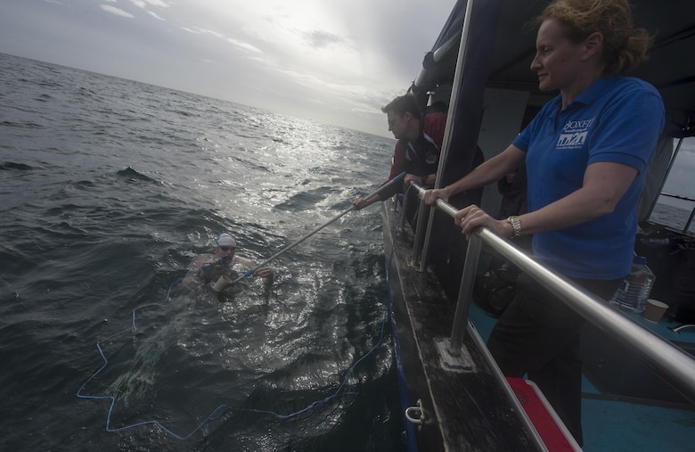 Maj. Casey Bowen (left), a dermatologist with the 59th Medical Wing, drinks some liquid as he swims across the English Channel Sept. 26, 2016. Bowen successfully swam from the shoreline of Dover, England, to the French coast, and completing his swim across the channel. (DoD News photo/Tech. Sgt. Brian Kimball)