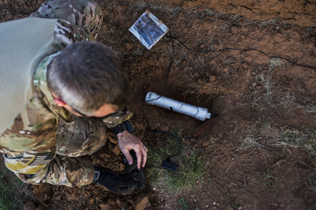 Master Sgt. Jeremy Phillips, 27th Special Operations Civil Engineer Squadron Explosive Ordnance Disposal flight chief, places a simulated improvised explosive device in the ground during IED training at Melrose Air Force Range, N.M., Sept. 28, 2016. An IED is any bomb constructed and deployed in other ways than conventional military methods and commonly used as a roadside bomb. (U.S. Air Force photo by Senior Airman Luke Kitterman/Released)