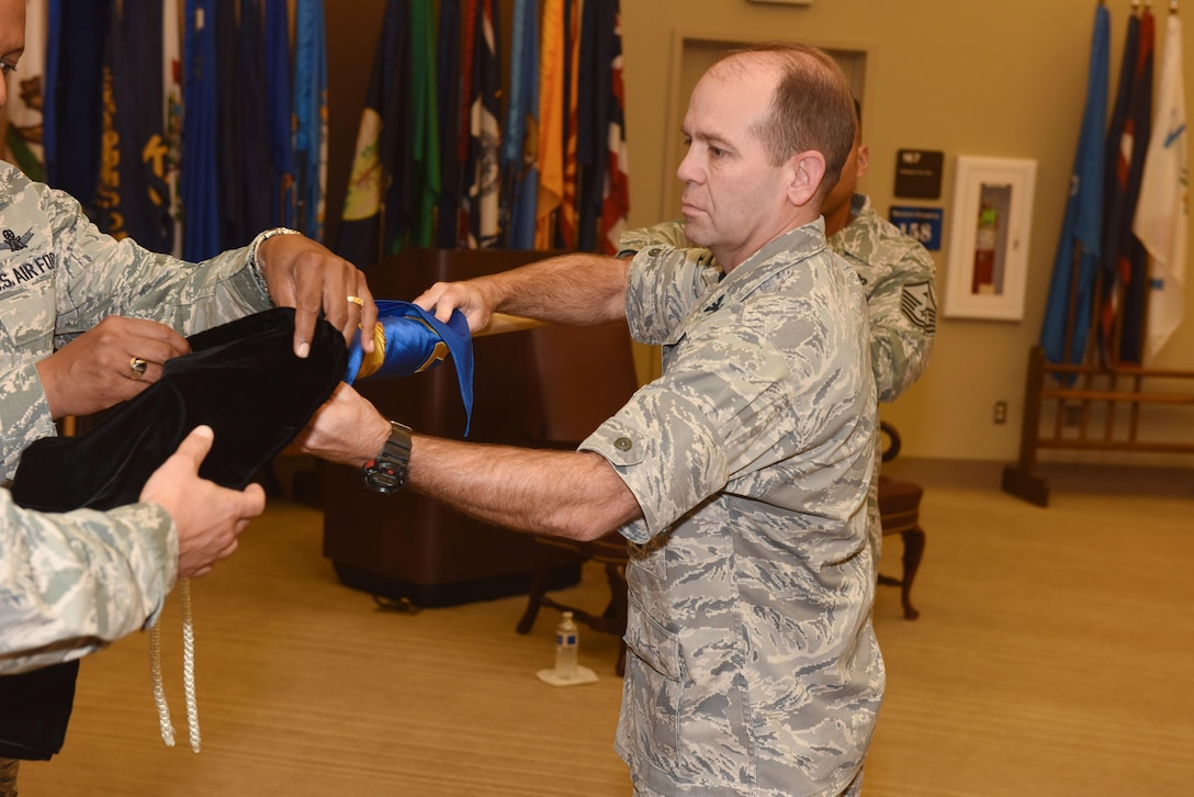 Col. Craig Ramsey, 576th Flight Test Squadron commander, secures the old 576th FLTS flag before the unveiling of a new one during a realignment ceremony, Sept. 30, 2016, Vandenberg Air Force Base, Calif. The Air Force Global Strike Command Operations Directorate transferred administrative control of the 576th FLTS to the 20th Air Force commander, effective Oct. 1. (U.S. Air Force photo by Airman 1st Class Robert J. Volio/Released)