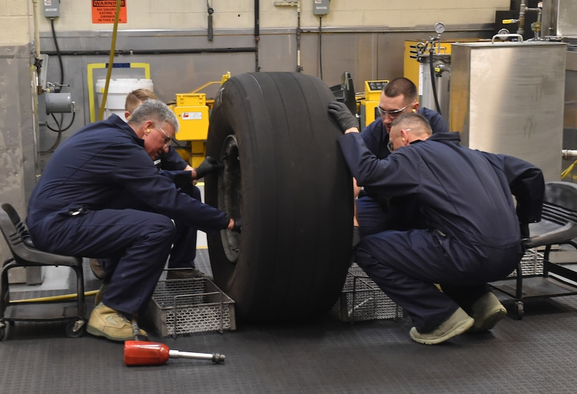 U.S. Air Force Lt. Gen. Sam Cox, 18th Air Force commander, and Chief Master Sgt. Todd Petzel, 18th AF command chief, receive a hands-on lesson on repairing a C-17 tire Sept. 29, 2016, at Joint Base Charleston, South Carolina. Airmen from the 437th Maintenance Squadron ensure that every part of the aircraft is in good working order and safe to use.