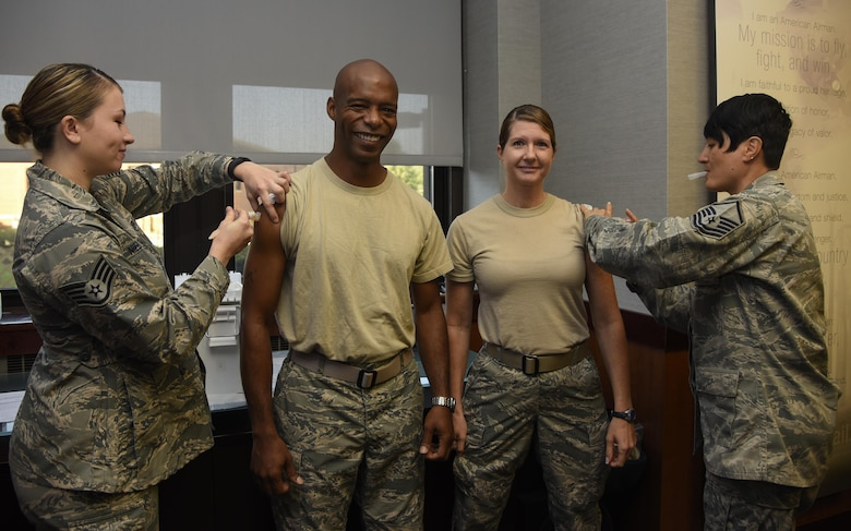 Chief Master Sgt. Nathaniel Perry, center left, 779th Medical Group command chief, and Chief Master Sgt. Beth Topa, center right, 11th WG command chief, receive their vaccinations to kick-off the flu shot season at Joint Base Andrews, Md., Oct. 3, 2016. Base leadership received their immunization to kick-off the flu shot drive for retirees, active duty and dependents slated for Oct. 17-18 from 8 a.m. to 4 p.m. at the base theater. The commanders' shots were given by Staff Sgt. Mallery Niebanck, left, 779th Medical Group allergy and immunization technician, and Master Sgt. Nancy Turner, right, 779th Medical Group immunization backup technician. (U.S. Air Force photo by Airman 1st Class Valentina Lopez)