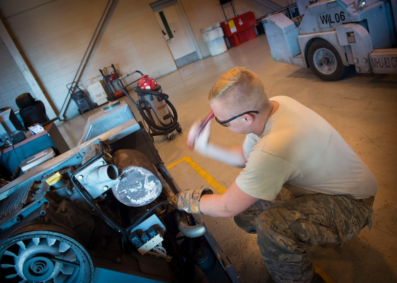 Senior Airman Miles Shepperd, an aerospace ground equipment journeyman with the 1st Special Operations Maintenance Squadron, works to remove an exhaust pipe from a munitions handling unit at the AGE hangar on Hurlburt Field, Fla., Oct. 3, 2016. An MHU is used to assist munitions Airmen with loading ammo onto aircraft. (U.S. Air Force photo by Senior Airman Krystal M. Garrett)