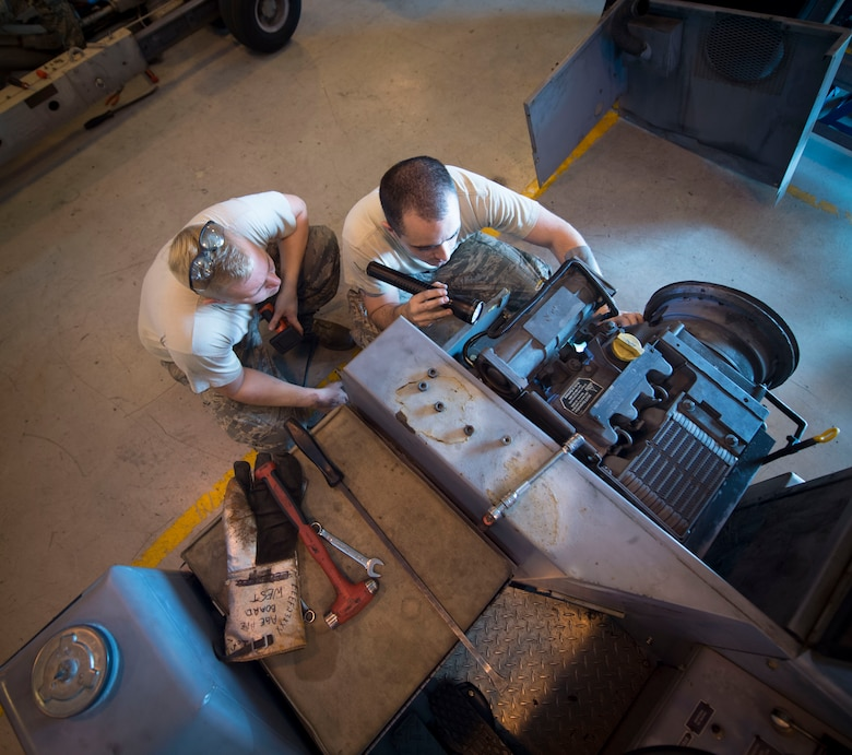 Senior Airman Miles Shepperd, left, an aerospace ground equipment journeyman with the 1st Special Operations Maintenance and Staff Sgt. Robert Pennington, an AGE craftsman, look inside a munitions handling unit at the AGE hangar on Hurlburt Field, Fla., Oct. 3, 2106. An MHU is used to assist munitions Airmen with loading munitions onto aircraft. (U.S. Air Force photo by Senior Airman Krystal M. Garrett)