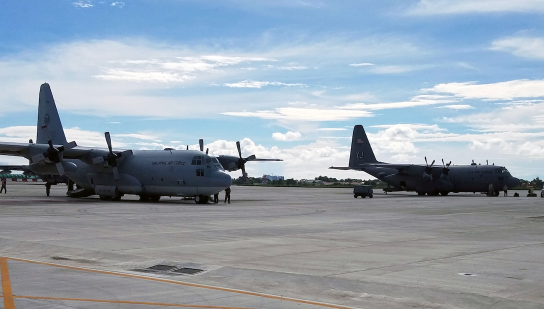 A U.S. Air Force C-130 aircraft from Yokota Air Base, Japan, and a Philippine Air Force C-130 aircraft from Mactan-Benito Ebuen Air Base, Lapu-Lapu City, Philippines, are prepped to support the first bilateral mission of the current iteration of a rotational Air Contingent at Brigadier General Benito N Ebuen Air Base, Philippines, Sept 26, 2016. The Air Contingent is helping build the capacity of the Philippine Air Force and increases joint training, promotes interoperability and provides greater and more transparent air and maritime situational awareness to ensure safety for military and civilian activities in international waters and airspace. Its missions include air and maritime domain awareness, personnel recovery, combating piracy, and assuring access to the air and maritime domains in accordance with international law. (U.S. Air Force photo by Tech. Sgt. George Maddon)