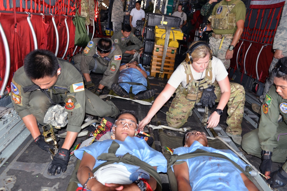 U.S. and Philippine Air Force members work together to rapidly secure patient litters in the midst of an engine running onload drill as part of a mass casualty response training exercise during the current iteration of a rotational Air Contingent at Brigadier General Benito N Ebuen Air Base, Philippines Sept. 29, 2016. The Air Contingent is helping build the capacity of the Philippine Air Force and increases joint training, promotes interoperability and provides greater and more transparent air and maritime situational awareness to ensure safety for military and civilian activities in international waters and airspace. Its missions include air and maritime domain awareness, personnel recovery, combating piracy, and assuring access to the air and maritime domains in accordance with international law. (U.S. Air Force photo by Capt. Mark Lazane)
