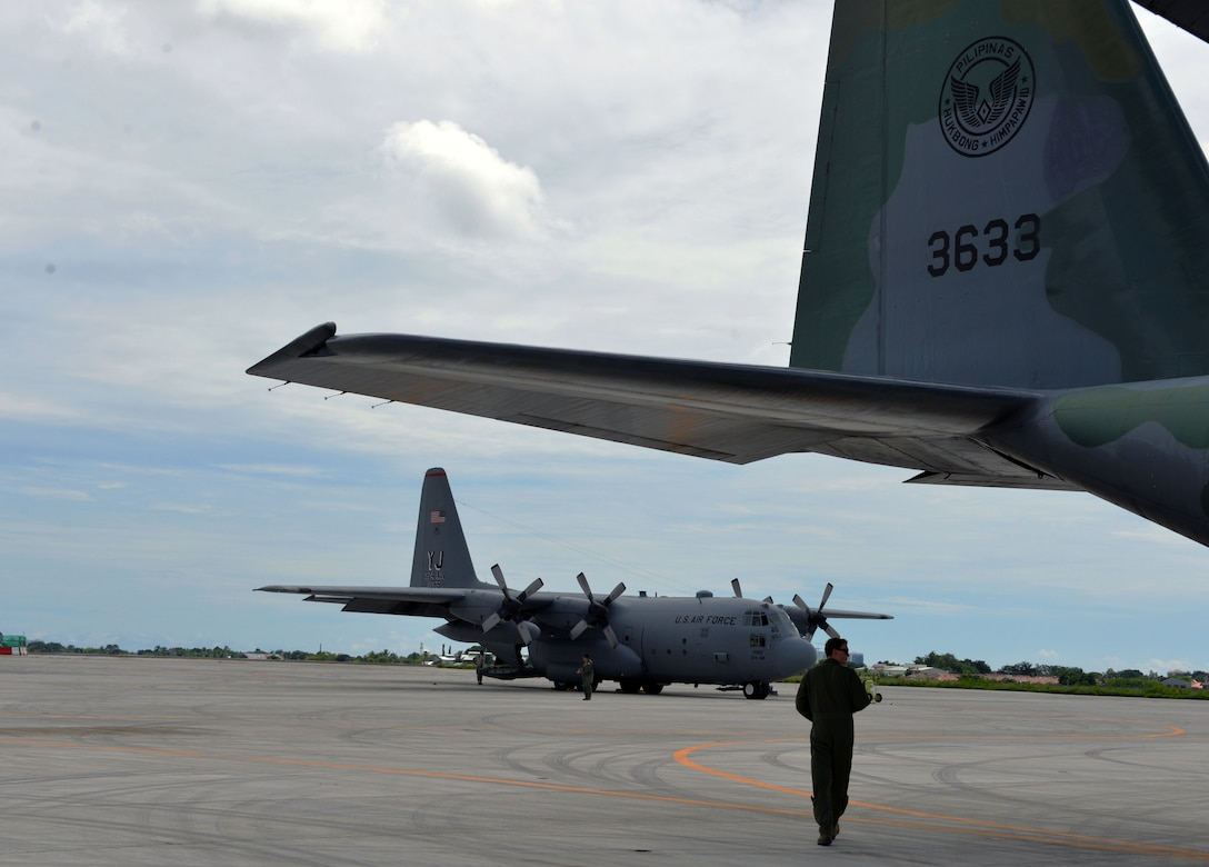 U.S. Air Force Capt. Mike Dzyndra, mission navigator, 36th Airlift Squadron, 374th Airlift Wing, Yokota Air Base, Japan, walks under the tail of a Philippine Air Force C-130 aircraft as a mass casualty response drill takes place during the rotational Air Contingent at Brigadier General Benito N Ebuen Air Base, Philippines, Sept. 29, 2016. The Air Contingent is helping build the capacity of the Philippine Air Force and increases joint training, promotes interoperability and provides greater and more transparent air and maritime situational awareness to ensure safety for military and civilian activities in international waters and airspace. Its missions include air and maritime domain awareness, personnel recovery, combating piracy, and assuring access to the air and maritime domains in accordance with international law. (U.S. Air Force photo by Capt. Mark Lazane)