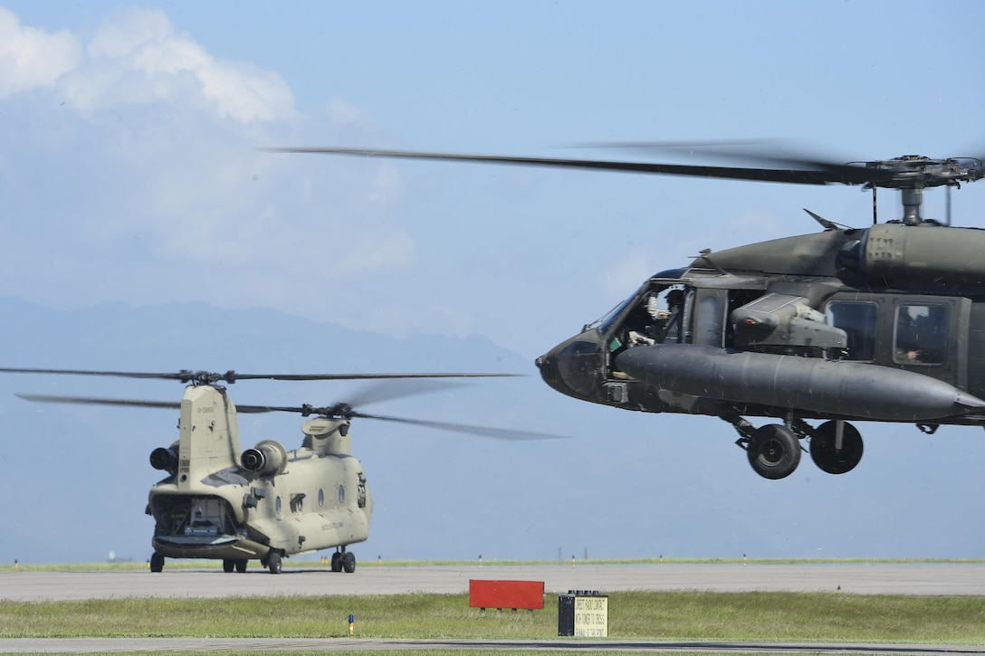 A UH-60 Blackhawk and a CH-47 Chinook helicopters assigned to Joint Task Force-Bravo's 1st Battalion, 228th aviation regiment, prepare to launch from Soto Cano Air Base, Honduras, Oct. 4, 2016, to stage at the Grand Cayman Islands to provide airlift capabilities for Hurricane Matthew relief efforts if requested by the U.S. Agency for International Development's Office of Foreign Disaster Assistance. The mission of Joint Task Force-Bravo includes being prepared to support disaster relief operations in Central America, South America and the Caribbean, when directed by SOUTHCOM. (U.S. Air Force photo by Staff Sgt. Siuta B. Ika)