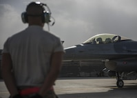 Senior Airman Jean Alonso, 455th Expeditionary Aircraft Maintenance Squadron crew chief, waits to marshal an F-16C Fighting Falcon, Bagram Airfield, Afghanistan, Oct. 5, 2016. Tactical aircraft maintenance technicians otherwise known as crew chiefs are the care takers of the aircraft. They inspect and prepare the aircraft and ensure it is ready to fly at a moment's notice so pilots can safely and effectively complete their mission. (U.S. Air Force photo by Senior Airman Justyn M. Freeman)