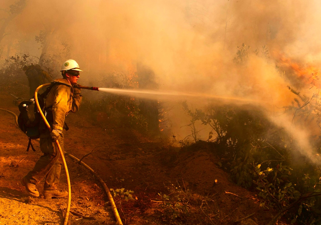 A firefighter suppresses hot spots during the 2014 wildfire season in California. Defense Logistics Agency Troop Support began providing firefighting and other materiel to wildland firefighters with the U.S. Forest Service in 2014.