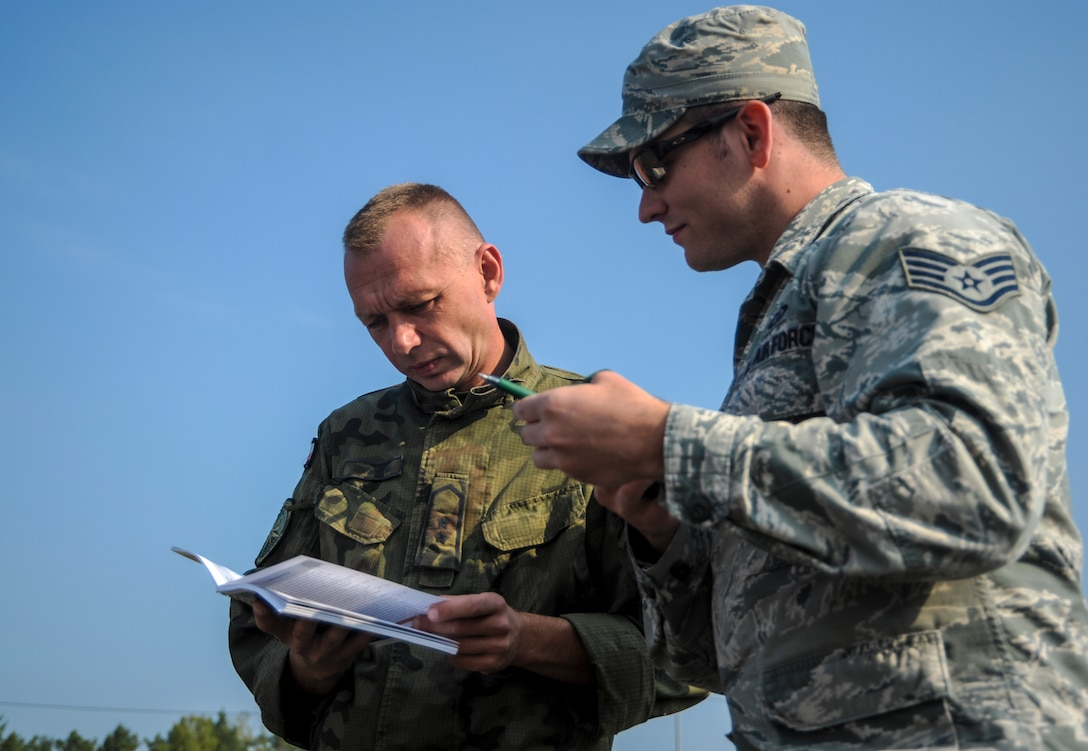 U.S. Air Force Staff Sgt. Joshua Young, 7th Weather Squadron, Detachment 2 weather forecaster, and Polish armed forces Warrant Officer Andrzej Kozlowski, weather forecaster, review a U.S. Army Weather Support Handbook during exercise Cadre Focus 16.2 in Grafenwoehr, Germany, Sept. 27, 2016. Cadre Focus 16.2 is the first time the 7th WS and 7th Expeditionary Weather Squadron invited their Polish and German counterparts to train with them as they refresh skills they need to work with the U.S. Army. (U.S. Air Force photo by Staff Sgt. Timothy Moore)