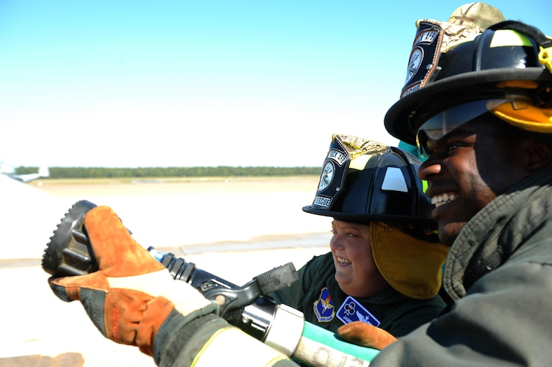 (From right) U.S. Air Force Senior Airman Marcus Scriven, 19th Mission Support Group Fire Department firefighter, helps James Rogers, 17, operate the fire hose during his tour of the fire department Oct. 3, 2016, at Little Rock Air Force Base, Ark. Rogers received the tour as part of the Pilot for a Day program, which provides children who have serious or chronic illnesses an opportunity to be part of a flying squadron for an entire day.