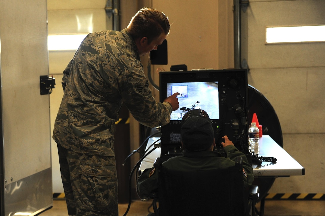 (From left) U.S. Air Force Senior Airman Htyler Kelly, 19th Civil Engineer Squadron Explosive Ordinance Disposal technician, explains how an EOD robot works to James Rogers, 17, during his Pilot for a Day visit Oct. 3, 2016, to Little Rock Air Force Base, Ark. Rogers received the tour as part of the Pilot for a Day program, which provides children who have serious or chronic illnesses an opportunity to be part of a flying squadron for an entire day.