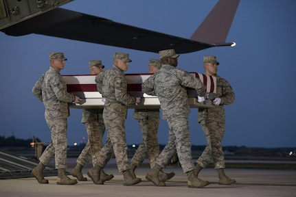 An Air Force carry team carries the remains of Maj. Troy Gilbert Oct. 3, 2016, at Dover Air Force Base, Del. Gilbert was killed Nov. 27, 2006, when his F-16C Fighting Falcon crashed 20 miles northwest of Baghdad. U.S. forces were able to return the F-16 pilot's remains approximately 10 years after he was killed in combat operations saving the lives of U.S. service members and coalition allies. (U.S. Air Force Photo by Senior Airman Aaron J. Jenne)