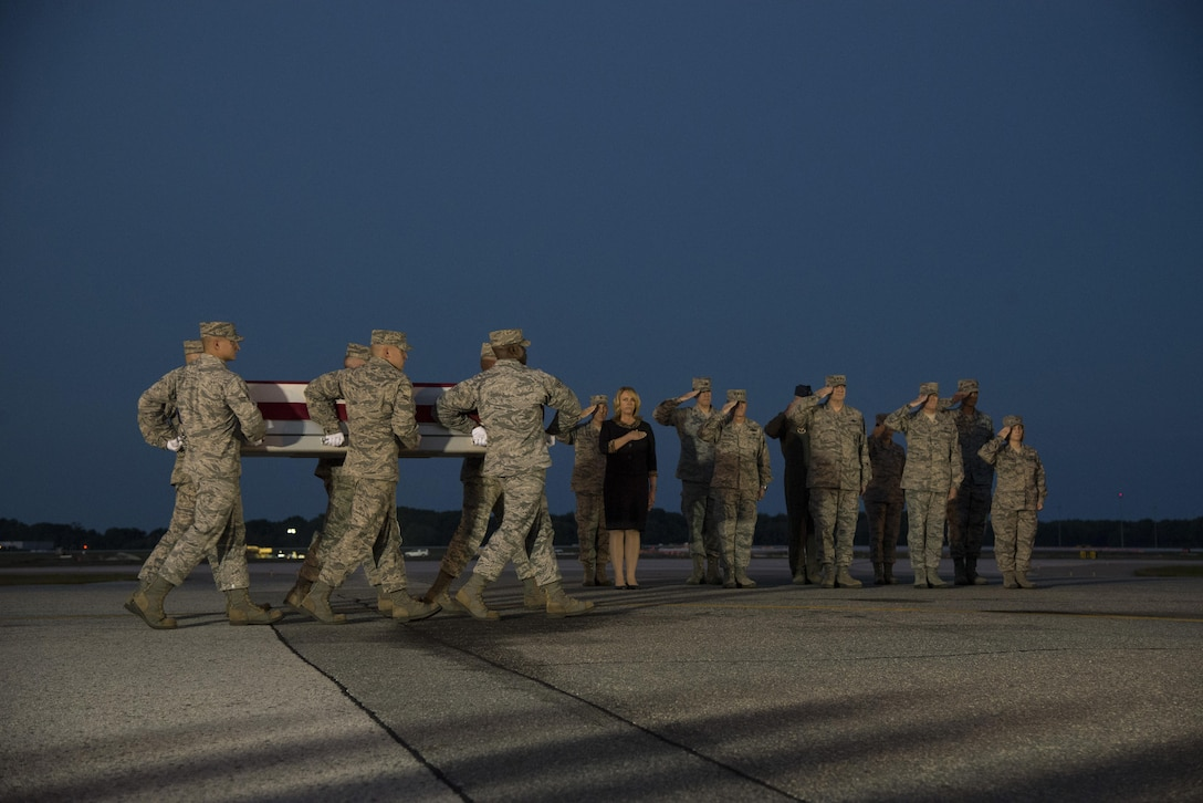 An Air Force carry team carries the remains of Maj. Troy Gilbert as the official party renders honors during a dignified transfer Oct. 3, 2016, at Dover Air Force Base, Del. Maj. Troy Gilbert, an F-16 Fighting Falcon pilot, was killed Nov. 27, 2006, in an F-16 crash 30 miles southwest of Balad Air Base, Iraq. Gilbert was the standardization and evaluation chief for the 332nd Expeditionary Operations Group and was deployed from the 309th Fighter Squadron from Luke Air Force Base, Ariz. (U.S. Air Force Photo by Senior Airman Aaron J. Jenne)