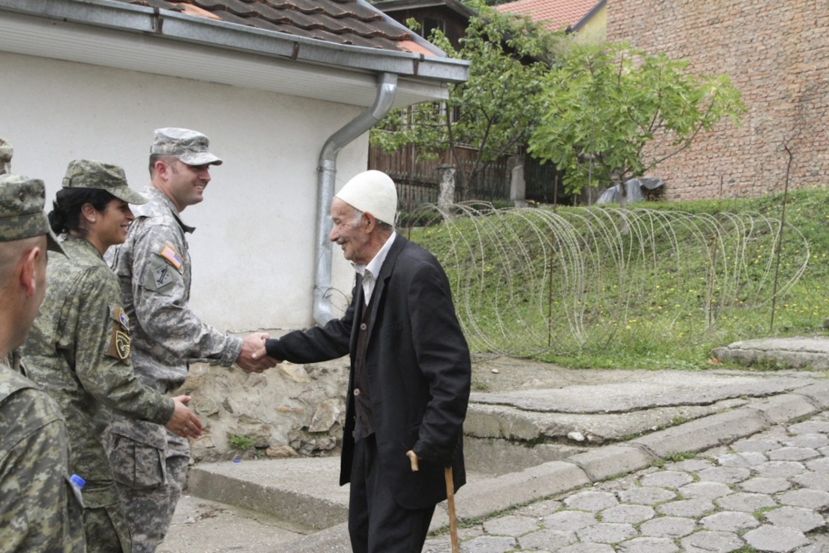 Sgt. 1st Class Obadiah Meyers (middle), Iowa National Guard (IANG) soldier from the 67th Troop Command, shakes hands with a resident of Prizren, Kosovo (right) while on a tour of the city during the IANG staff ride on Monday, September 12, 2016. Staff Sgt. Valbona Kerolli (left), nurse with the Kosovo Security Force (KSF) Medical Company, prepares to shake hands with the gentleman next. Iowa and the Republic of Kosovo have partnered through the National Guard Bureau State Partnership Program since 2011.
