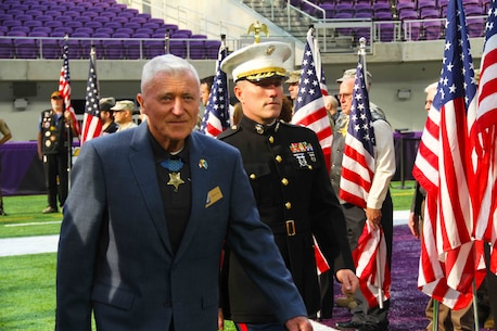 Major Andrew Nicholson, commanding officer of Marine Corps Recruiting Station Twin Cities, escorts Medal of Honor recipient Wesley Fox, a retired Marine Corps colonel, during the Twin Cities Medal of Honor Ceremony at the U.S. Bank Stadium, Oct. 5. Fox received the Medal of Honor for Heroic actions during the Vietnam War.