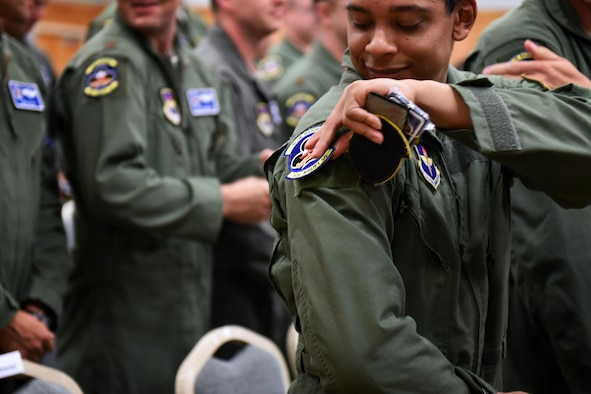 U.S. Air Force Staff Sgt. Terrence Greene, 62nd Airlift Squadron loadmaster instructor, places a new 62nd AS patch on his flight suit during the 48th Airlift Squadron transition ceremony Sept. 30, 2016, at Little Rock Air Force Base, Ark. With the 314th Airlift Wing transitioning away from the C-130H model and being the sole providers of C-130J training, the 48th Airlift Squadron personnel have become members of the 62nd AS.