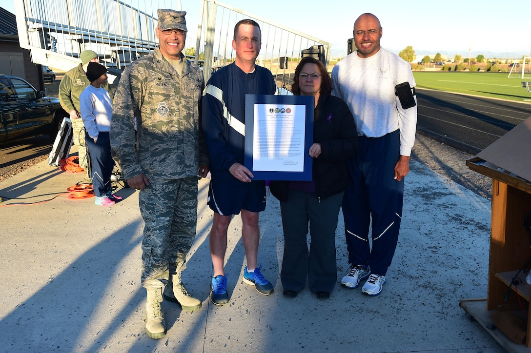 Buckley Air Force Base leadership stands with a domestic violence proclamation before a Domestic Violence Awareness Month 5K Run/Walk Oct. 5, 2016, at the outdoor track on Buckley Air Force Base, Colo. National Domestic Violence Awareness Month aims to make America a country where no one suffers the hurt and hardship that domestic violence causes. (U.S. Air Force photo by Airman 1st Class Gabrielle Spradling/Released)