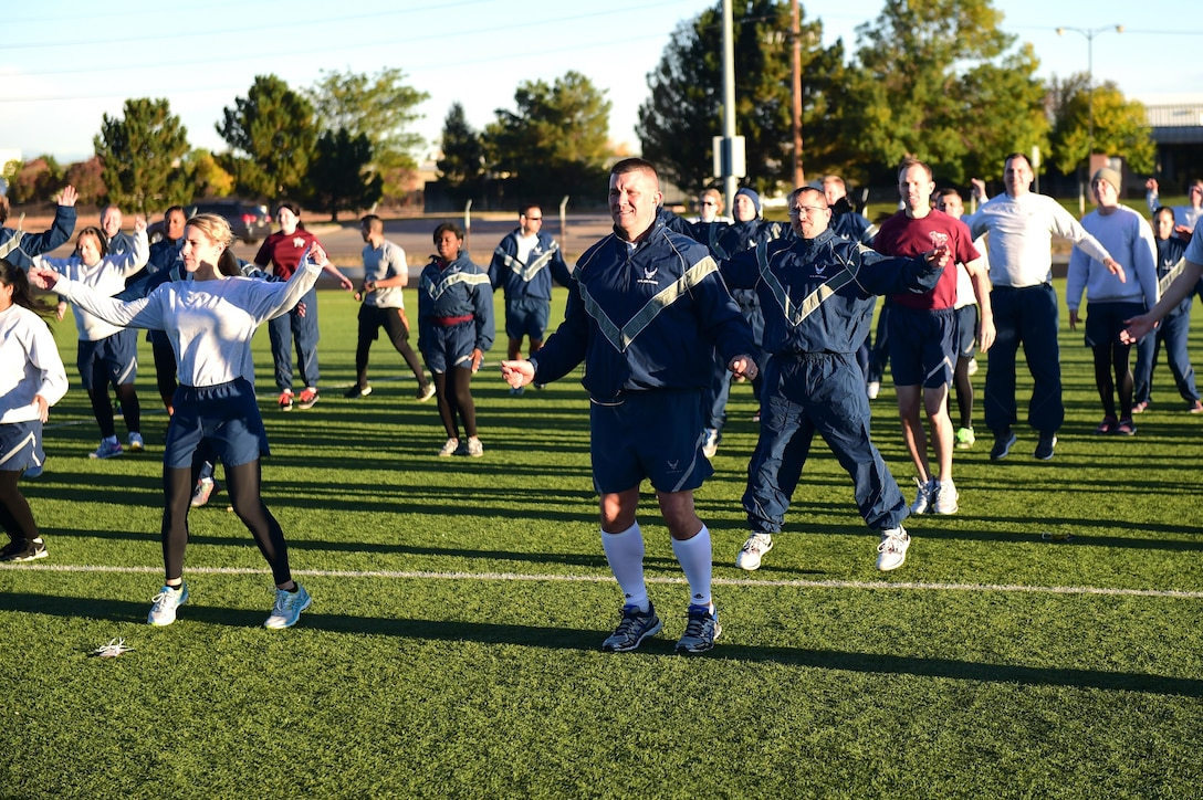 Team Buckley members stretch before participating in a Domestic Violence Awareness Month 5K Run/Walk Oct. 5, 2016, at the outdoor track on Buckley Air Force Base, Colo. The 460th Medical Group Family Advocacy Program hosted the run/walk to kick off National Domestic Violence Awareness Month, which is observed in October. (U.S. Air Force photo by Airman 1st Class Gabrielle Spradling/Released)
