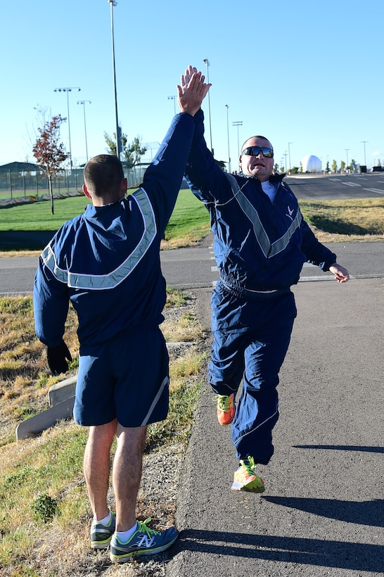 Chief Master Sgt. Mark Fousek, 460th Medical Group superintendent, gives a participant a high five during a Domestic Violence Awareness Month 5K Run/Walk Oct. 5, 2016, at the outdoor track on Buckley Air Force Base, Colo. Participants either ran or walked to bring awareness to those who, according to National Coalition Against Domestic Violence statistics, on an average day, make the more than 20,000 phone calls that are placed to domestic violence hotlines nationwide. (U.S. Air Force photo by Airman 1st Class Gabrielle Spradling/Released)