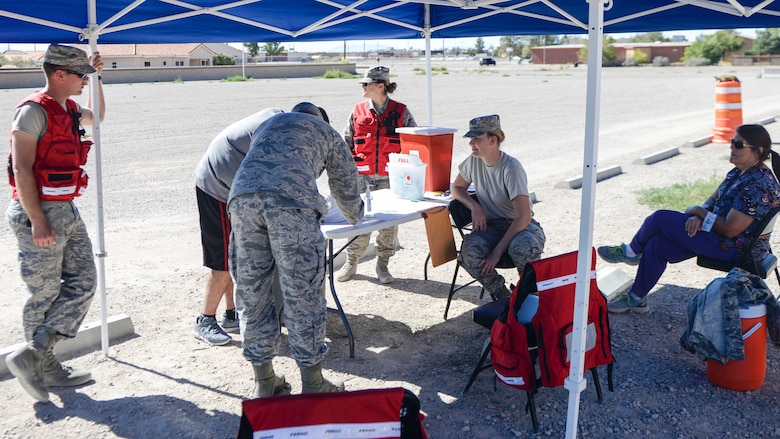 Two Airmen sign their individual medical paperwork at the Holloman drive-thru immunization clinic Oct. 4, 2016. The 49th Medical Group set up the drive-thru clinic to make it easier for active duty Holloman Airmen to obtain their annual flu shot. The 49th MDG staff administered the influenza vaccine to 720 Airmen. (U.S. Air Force photo by Airman 1st Class Alexis P. Docherty)