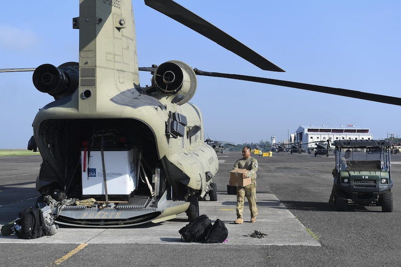 A CH-47 Chinook helicopter crew chief assigned to Joint Task Force-Bravo's 1st Battalion, 228th Aviation Regiment, prepares to a load a box at Soto Cano Air Base, Honduras, Oct. 5, 2016, in preparation for a flight to the Grand Cayman Islands and eventually on to Haiti to provide airlift capabilities for Hurricane Matthew relief efforts as requested by the U.S. Agency for International Development's Office of Foreign Disaster Assistance. The mission of Joint Task Force-Bravo includes being prepared to support disaster relief operations in Central America, South America and the Caribbean, when directed by SOUTHCOM. (U.S. Air Force photo by Staff Sgt. Siuta B. Ika)