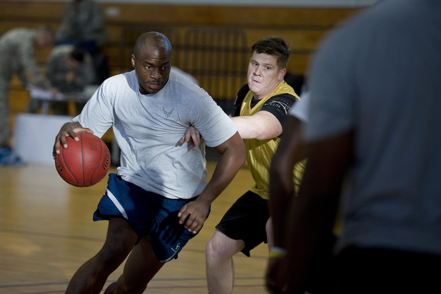 U.S. Air Force Master Sgt. Brenton Williams, left, 51st Maintenance Group, drives the ball in during a 3 vs. 3 basketball game at Osan Air Base, Republic of Korea, Sept. 29, 2016. The 3 vs. 3 basketball game was part of Osan Cup 2016, which was designed to build teamwork, resiliency, camaraderie and family.  (U.S. Air Force photo by Staff Sgt. Jonathan Steffen)