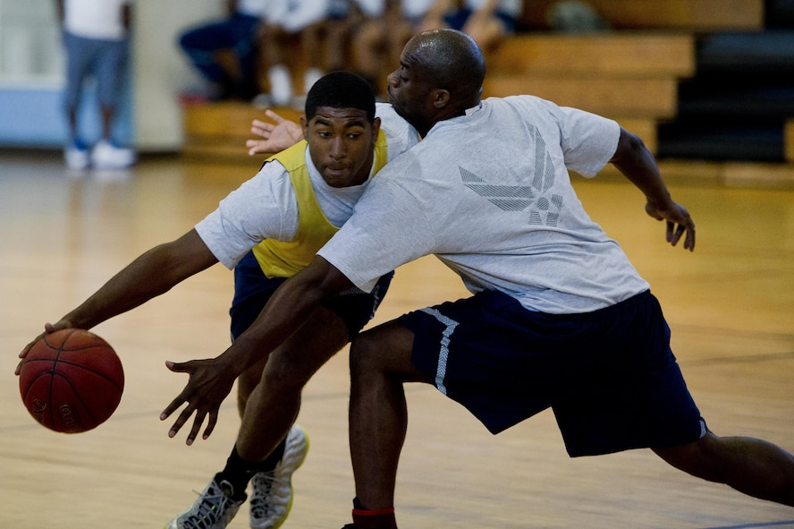 U.S. Air Force Airman 1st Class Gary Washington, 51st Munitions Squadron, pushes past a defender from the 51st Security Forces Squadron during a 3 vs. 3 basketball ball game at Osan Air Base, Republic of Korea, Sept. 29, 2016. The 3 vs. 3 basketball game was part of Osan Cup 2016, which also included events like darts, pool and paintball.  (U.S. Air Force photo by Staff Sgt. Jonathan Steffen)