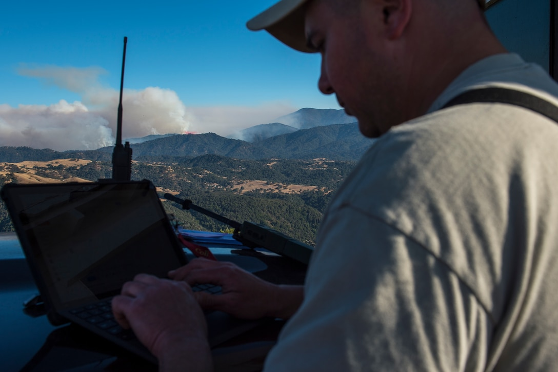Lt. Col. Shawn Scott, distributed real-time infrared program manager, emails data files to interagency firefighting commanders at the incident command post on the Soberanes Fire in Monterey County, California Aug. 02, 2016. The files sent are used to update, near real time, fire perimeter maps. This near real time data is one of the benefits of the DRTI mission. (U.S. Air National Guard photo by Tech. Sgt. Joshua C. Allmaras)