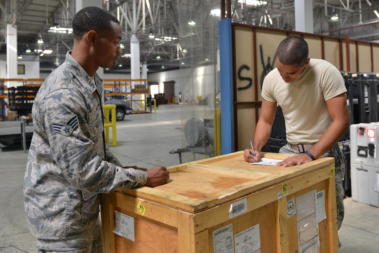 U.S. Air Force Senior Airman Turon Boyd (left), 39th Logistics Readiness Squadron service center journeyman, transfers property to an Airman in the supply warehouse Oct. 4, 2016, at Incirlik Air Base, Turkey. The supply warehouse harbors items such as aircraft parts and equipment necessary for aerial operations. (U.S. Air Force photo by Senior Airman John Nieves Camacho)