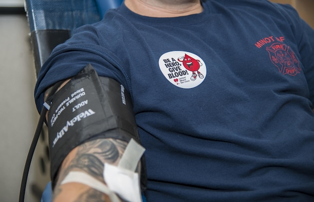 A 5th Civil Engineer Squadron firefighter donates blood during the Battle of the Badges blood drive at Minot Air Force Base, N.D., Sept. 30, 2016. During the blood drive, members earned points to determine who wins bragging rights and a trophy until next year's drive. (U.S. Air Force photo/Airman 1st Class Christian Sullivan)