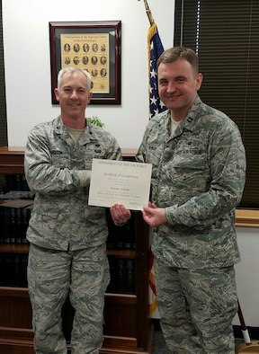 Lt. Col. Justin Dalton, 7th Bomb Wing staff judge advocate, presents Individual Mobilization Augmentee judge advocate Capt. Tomasz Nowak with his Air Force trial certification.