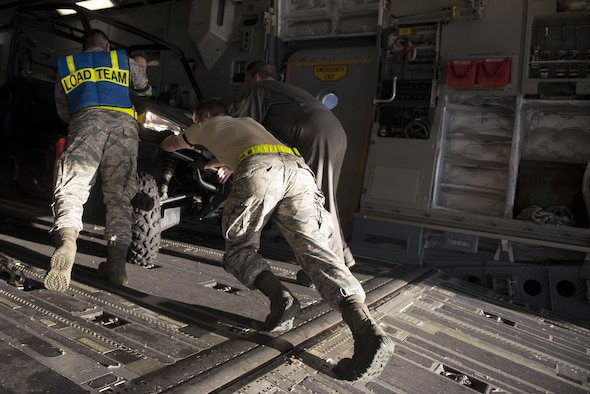 Loadmasters from the 6th Airlift Squadron and 305th Aerial Port Squadron secure an all-terrain vehicle on board a C-17 Globemaster III at Joint Base McGuire-Dix-Lakehurst, N.J., Oct. 3, 2016. The aircraft, with personnel and equipment from the 621st Contingency Response Wing, is bound for Haiti in response to Hurricane Matthew. The 621st CRW has units continuously on alert and ready to deploy anywhere in the world in support of emergency operations, such as hurricane relief, within 12 hours of notification. (U.S. Air Force photo/Airman 1st Class Zachary Martyn)