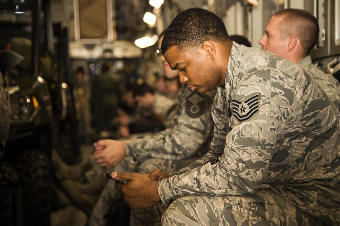 An Airmen assigned to the 621st Contingency Response Wing passes the time by playing with his phone as the C-17 Globemaster III he is sitting in is loaded with equipment at Joint Base McGuire-Dix-Lakehurst, N.J. October 6, 2016. The Airmen are on their way to Port-au-Prince, Haiti, in response to Hurricane Matthew. The CRW is highly-specialized in rapidly deploying personnel to quickly open airfields and establish, expand, sustain, and coordinate air mobility operations alongside joint and intra-agency partners. (U.S. Air Force photo by Tech. Sgt. Gustavo Gonzalez/Released)