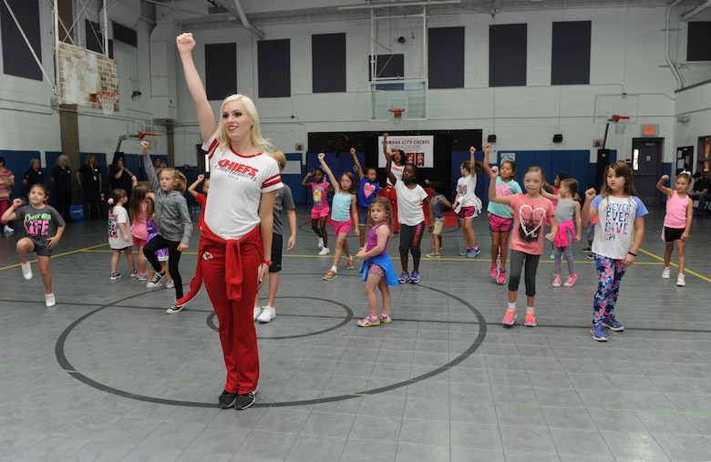 Sarah, Kansas City Chiefs cheerleader, demonstrates a cheer move during a cheer clinic at the youth center Oct. 1, 2016, on Keesler Air Force Base, Miss. The NFL cheerleaders visited Keesler to learn about the mission, hold a cheer clinic and participate in a fashion show at the base exchange. (U.S. Air Force photo by Kemberly Groue/Released)