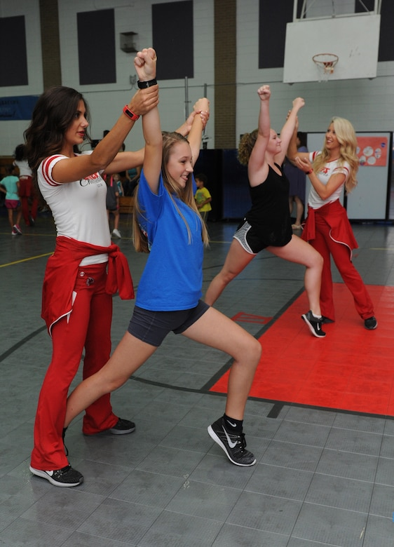 Katrina and Claire, Kansas City Chiefs Cheerleaders, assist participants with a cheer move during a cheer clinic at the youth center Oct. 1, 2016, on Keesler Air Force Base, Miss. The NFL cheerleaders visited Keesler to learn about the mission, hold a cheer clinic and participate in a fashion show at the base exchange. (U.S. Air Force photo by Kemberly Groue/Released)