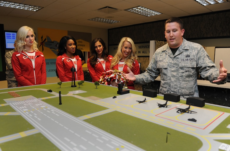 Tech. Sgt. Korey Papa, 334th Training Squadron instructor, shows an airfield model to Kansas City Chiefs cheerleaders during a tour at Cody Hall Sept. 30, 2016, on Keesler Air Force Base, Miss. The NFL cheerleaders visited Keesler to learn about the mission, hold a cheer clinic at the youth center and participate in a fashion show at the base exchange. (U.S. Air Force photo by Kemberly Groue/Released)