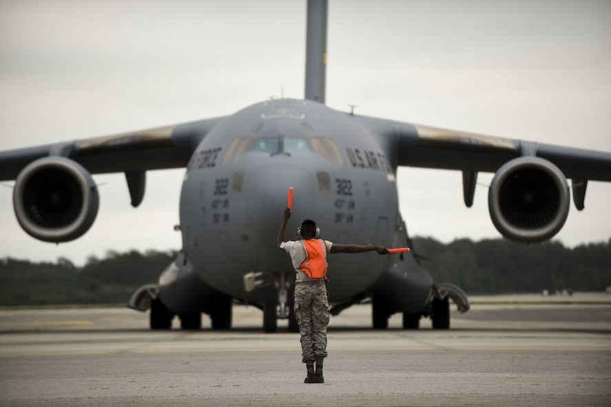 A maintainer from the 437th Air Craft Maintenance Squadron marshals out a Joint Base Charleston C-17 Globemaster III as it is evacuated to Fort Campbell, KY on Oct. 6, 2016 to continue the mission of rapid global mobility during Hurricane Matthew. Due to Hurricane Matthew, a Limited Evacuation Order of South Carolina Hurricane Evacuation Zones was issued by the Commander, Joint Base Charleston. All Joint Base personnel are expected to evacuate the area and will return once damage is assessed and it's safe to return.