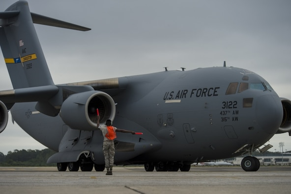 A maintainer with the 437th Aircraft Maintenance Squadron marshals out a Joint Base Charleston C-17 Globemaster III as it is evacuated to Fort Campbell, Ky., on Oct. 6, 2016, so they can continue their mission of rapid global mobility during Hurricane Matthew. Due to Hurricane Matthew, a Limited Evacuation Order of South Carolina Hurricane Evacuation Zones was issued by the Commander, Joint Base Charleston. All Joint Base personnel are expected to evacuate the area and will return once damage has been assessed and it's safe to return.