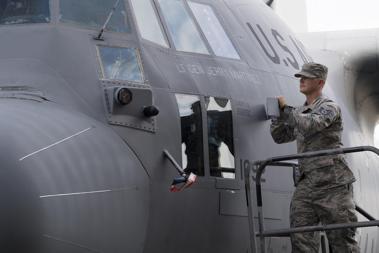 Staff Sgt. Kenneth Sutton, 374th Aircraft Maintenance Squadron crew chief, unveils the name of the incoming United States Forces, Japan and 5th Air Force commander, on a C-130H Hercules at Yokota Air Base, Japan, Oct. 6, 2016, during the assumption of command ceremony. (U.S. Air Force photo by Yasuo Osakabe/Released)