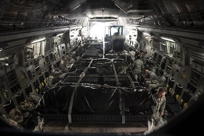 More than 30 members of the 621st Contingency Response Wing aboard a C-17 Globemaster III at Joint Base McGuire-Dix-Lakehurst, N.J. wait for equipment to be loaded on before takeoff on their way to Port-au-Prince, Haiti in response to Hurricane Matthew, October 6, 2016. The CRW is supporting the government of Haiti's request for humanitarian assistance. Once on the ground, the CRW will provide assistance by facilitating the movement of humanitarian aid and cargo.