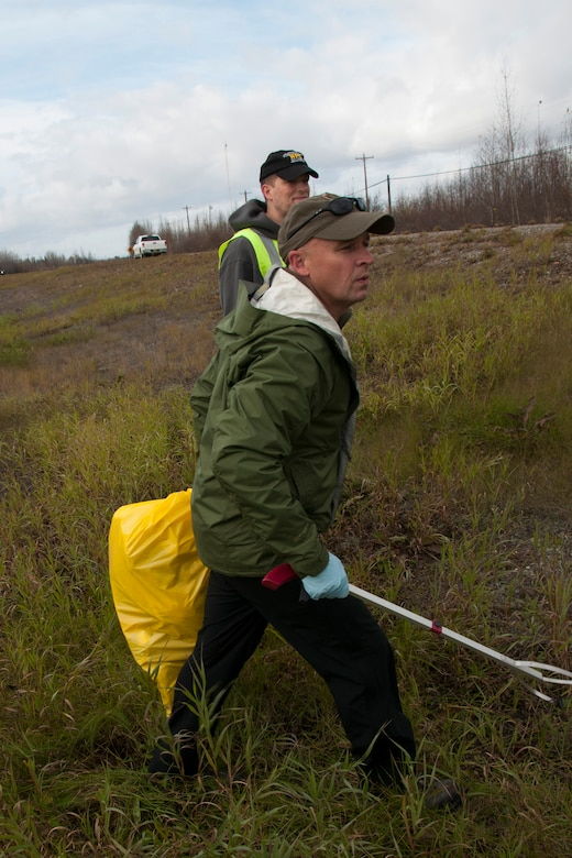 Chief Master Sgt. Phil Hunt and Master Sgt. James Meyer get ready to cross over the Richardson Highway between Eielson AFB and Fairbanks, Alaska on September 29, 2016. They and almost 20 other members of the 168th Wing, Alaska Air National Guard, plus a few family members, volunteered to pick up trash along the Top III Council's adopted mile of the highway, part of  Alaska Department of Transportation and Public Facilities Adopt-A-Highway program, which helps keep approximately 26 miles of the highway clean.