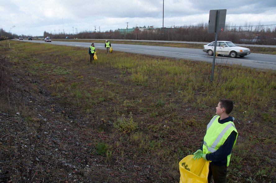 Zach Evans, son of Senior Airman Laura Evans, waits for his mom and Staff Sgt. Jeff Davidson from the 168th Wing, Alaska Air National Guard, to catch up as they worked together to pick up trash and debris along the southbound side of the Richardson Highway between Eielson AFB and Fairbanks, Alaska on September 29, 2016. The 168th's Top III, and at least 12 other organizations that work on Eielson, are active in the Alaska Department of Transportation and Public Facilities Adopt-A-Highway program and are helping keep approximately 26 miles of the highway clean.