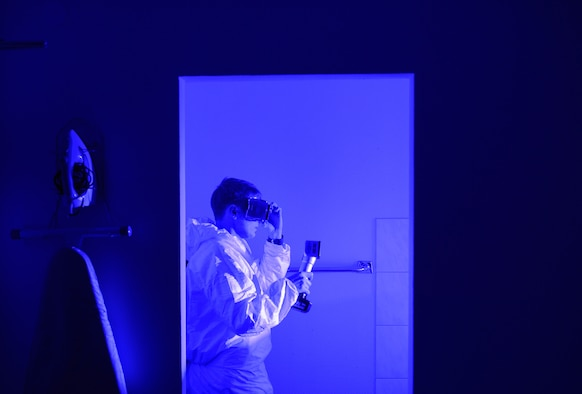 An Air Force Office of Special Investigations 4th Field Investigations Squadron agent utilizes an alternate light source during a mock crime scene at Ramstein Air Base, Germany, Oct. 6, 2016. Agents utilize light sources to search for biological fluids undetectable to the naked eye. The 4th FIS facilitate surprise mock crime scenes for six units within U.S Air Forces in Europe in order to assess agents' techniques and readiness. (U.S. Air Force photo by Senior Airman Nesha Humes)