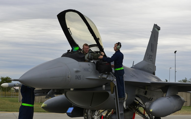 Airman 1st Class Nicholas Goncalves, 31st Aircraft Maintenance Squadron crew chief, takes equipment from Capt. Nathan Skavdal, 555th Fighter Squadron F-16 Fighting Falcon pilot, before starting his end-of-flight inspection on the aircraft at Aviano Air Base, Italy on Oct. 5, 2016. Airmen from the 31st AMXS inspect aircraft for physical, electrical and environmental defects to ensure the aircraft stays mission ready. (U.S. Air Force photo by Senior Airman Krystal Ardrey/Released)
