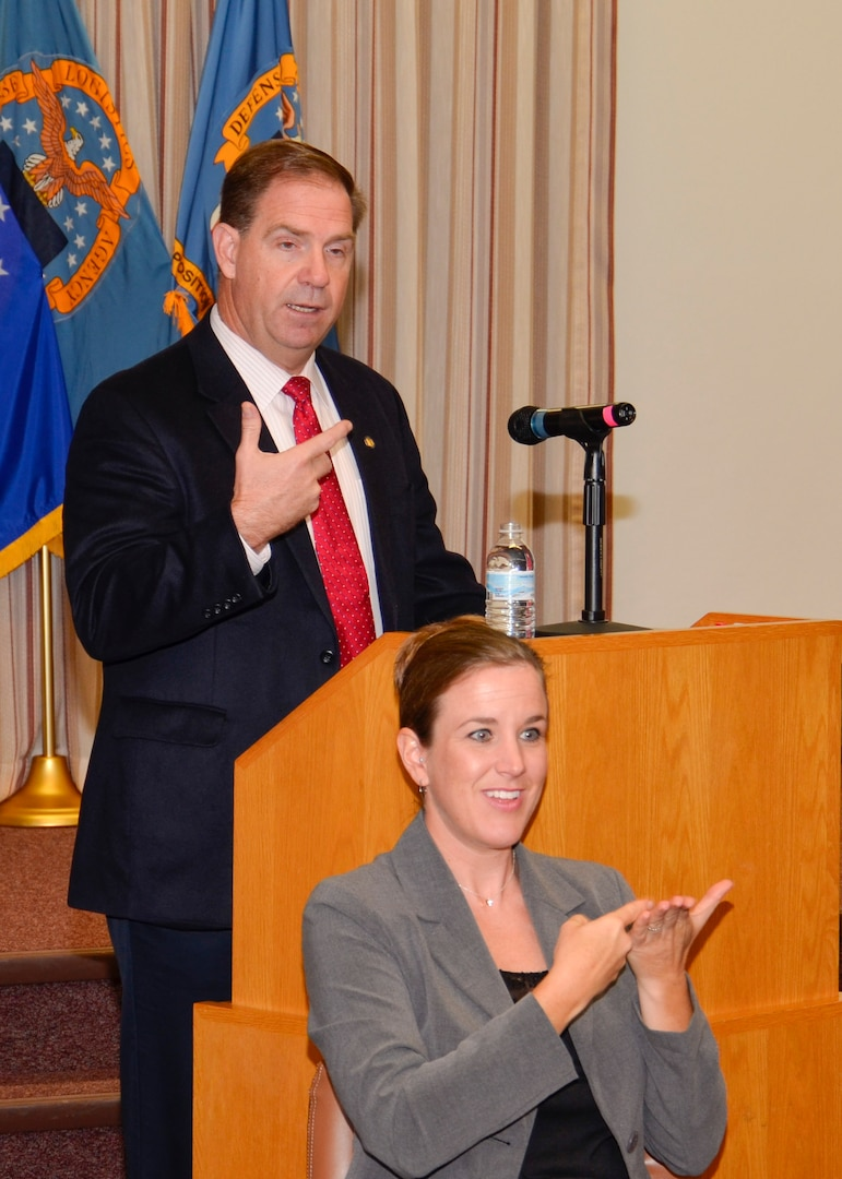 DLA Disposition Services Director Mike Cannon gives his opening remarks during the Hart-Dole-Inouye Federal Center's People With Disabilities program while Renelle Hansen interprets his remarks for deaf or hard of hearing audience members.